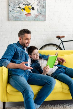 Photo for Smiling father and son in denim reading book on couch - Royalty Free Image