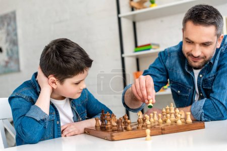 Photo for Father and son in denim sitting at table and playing chess at home - Royalty Free Image