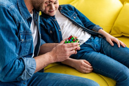 Photo for Partial view of father and son playing with toy cube while sitting on couch - Royalty Free Image