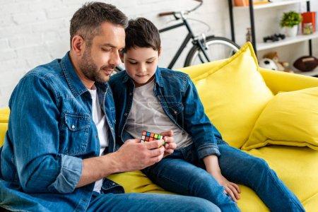 Foto de Padre e hijo sentados en el sofá y jugando con cubo de juguete en casa - Imagen libre de derechos