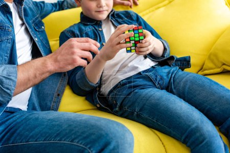 Photo for Cropped view of father and son sitting on couch and playing with toy cube at home - Royalty Free Image