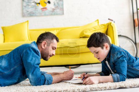Photo for Father and son lying on carpet and drawing in Living Room - Royalty Free Image