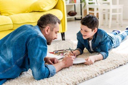 Photo pour Père et fils se trouvant sur le tapis et dessinant dans la salle de séjour - image libre de droit