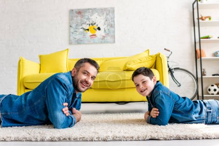 Photo for Happy father and son in denim with crossed arms lying on carpet and looking at camera at home - Royalty Free Image