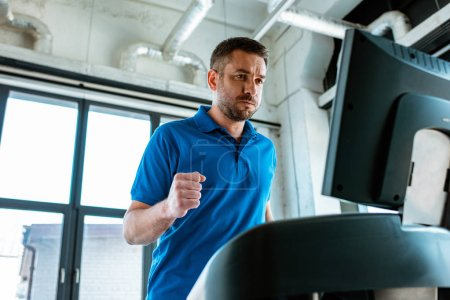Photo for Handsome man running on treadmill at gym - Royalty Free Image