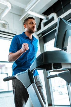 Photo for Handsome man working out on treadmill at gym - Royalty Free Image