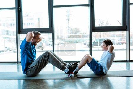 Photo pour Le père et le fils faisant s'asseoir l'exercice sur des tapis de forme physique à la gymnastique - image libre de droit