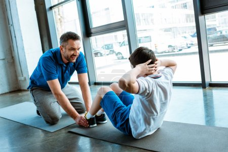 Photo for Father helping son with sit up exercise at gym - Royalty Free Image
