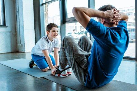 Photo pour Fils souriant aidant le père s'asseyant sur le tapis de forme physique et faisant s'asseoir l'exercice à la gymnastique - image libre de droit