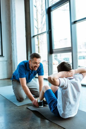 Photo for Father helping son sitting on fitness mat and doing sit up exercise at gym - Royalty Free Image
