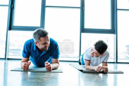 Photo pour Père et fils faisant l'exercice de planche sur des tapis de forme physique à la gymnastique - image libre de droit