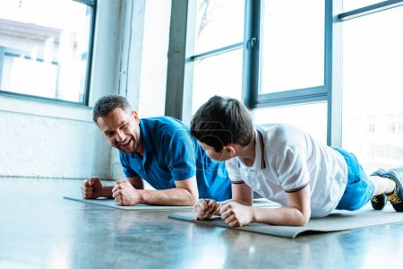 Photo for Father and son doing plank exercise on fitness mats at gym - Royalty Free Image
