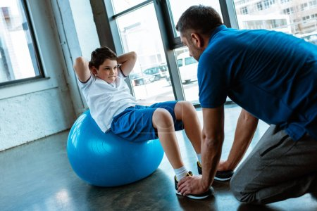 Photo for Father helping son sitting on fitness ball and doing sit up exercise at gym - Royalty Free Image
