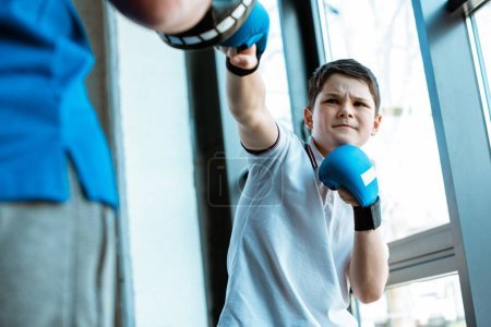 Photo for Selective focus of boy in boxing gloves training with coach at gym - Royalty Free Image