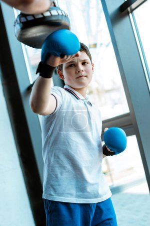Photo for Boy in boxing gloves training with coach at gym - Royalty Free Image