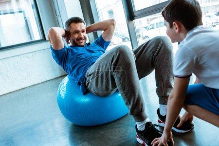 Photo pour Fils aidant le père s'asseyant sur la bille de forme physique et faisant s'asseoir l'exercice à la gymnastique - image libre de droit