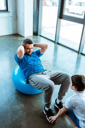 Photo for Son helping father sitting on fitness ball and doing sit up exercise at gym - Royalty Free Image