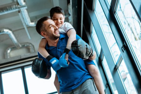 Photo pour Père donnant tour de ferroutage au fils souriant dans des gants de boxe à la gymnastique - image libre de droit