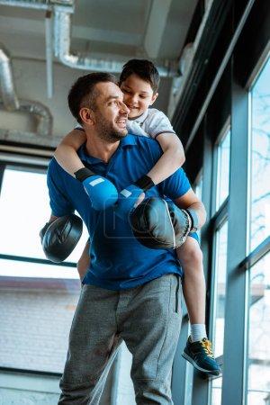 Photo pour Père heureux donnant tour de ferroutage au fils de sourire dans des gants de boxe à la gymnastique - image libre de droit