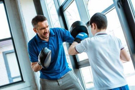 Photo pour Garçon dans des gants de boxe travaillant avec le père à la gymnastique - image libre de droit