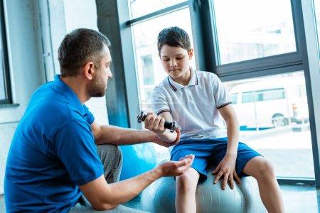 Photo pour Père aidant le fils sur l'exercice de tapis de forme physique avec l'haltère au centre sportif - image libre de droit