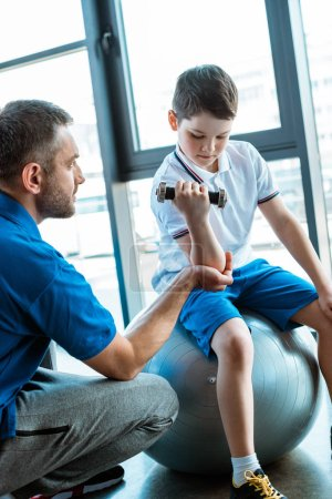 Photo for Father helping son on fitness mat exercising with dumbbell at sports center - Royalty Free Image