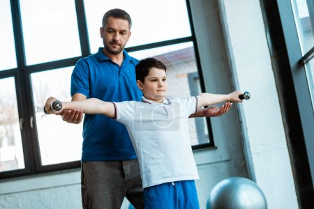 Photo for Father helping son exercising with dumbbells at gym - Royalty Free Image