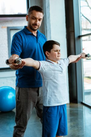 Photo for Father helping son working out with dumbbells at gym - Royalty Free Image