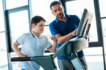 Photo for Father pointing at screen of treadmill while son running at sports center - Royalty Free Image