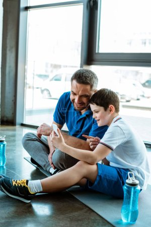 Photo for Smiling father and son sitting on fitness mat and using smartphone at gym - Royalty Free Image
