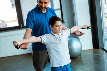 Photo for Father helping son exercising with dumbbells at sports center - Royalty Free Image