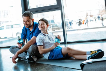 Photo for Smiling father and son sitting on fitness mat with sport bottles at gym - Royalty Free Image