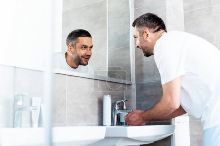 Photo for Handsome smiling man looking in mirror and washing hands in bathroom during morning routine - Royalty Free Image