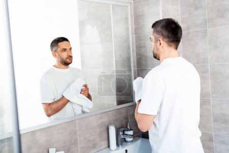 Photo for Handsome man wiping hands with towel in bathroom during morning - Royalty Free Image