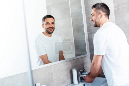 Photo for Handsome smiling man washing hands in bathroom during morning routine - Royalty Free Image