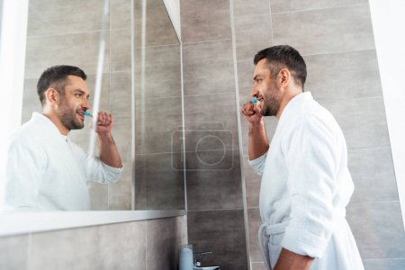 Photo for Handsome man in white bathrobe brushing teeth in bathroom during morning routine - Royalty Free Image