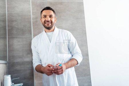 Photo pour Bel homme souriant en peignoir blanc avec brosse à dents regardant la caméra dans la salle de bain - image libre de droit