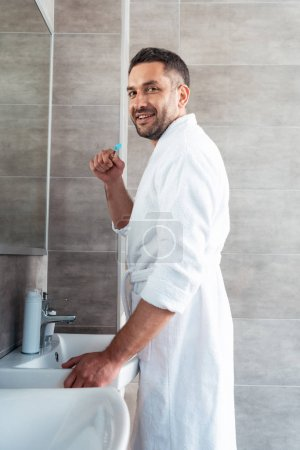 Photo for Handsome man in bathrobe looking at camera while brushing teeth during morning routine - Royalty Free Image