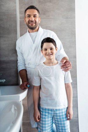 Photo pour Père et fils souriants dans des pyjamas regardant l'appareil-photo dans la salle de bains - image libre de droit