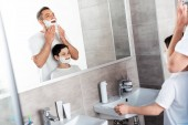 son and father with shaving cream on faces in bathroom