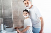smiling son and father with shaving cream on faces looking at camera in bathroom