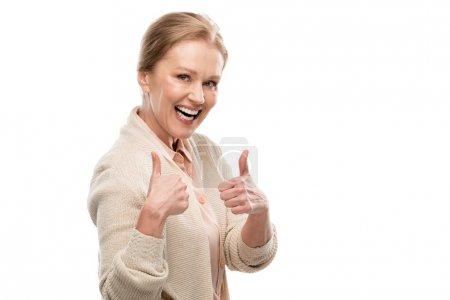 Photo pour Femme âgée moyenne excitée affichant le pouce vers le haut des signes d'isolement sur le blanc - image libre de droit