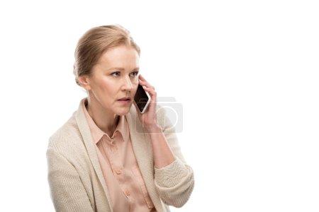 Photo pour Femme âgée moyenne concentrée parlant sur le smartphone isolé sur le blanc - image libre de droit