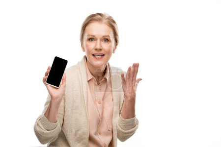 Photo for Middle aged woman Gesturing and showing smartphone with blank screen Isolated On White - Royalty Free Image