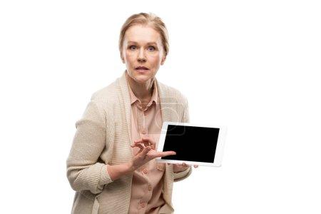 Photo pour Femme âgée moyenne confuse pointant avec le doigt à la tablette numérique avec l'écran blanc isolé sur le blanc - image libre de droit