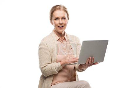 Kobieta w średnim wieku za pomocą laptopa i patrząc na aparat na białym tle