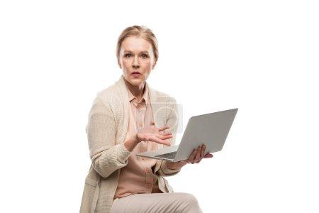 Photo pour Femme âgée moyenne confuse utilisant l'ordinateur portatif et Gesturing isolé sur le blanc - image libre de droit