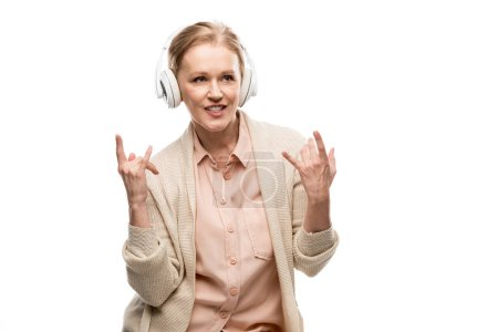 Photo for Middle aged woman in headphones listening music and showing rock signs Isolated On White - Royalty Free Image