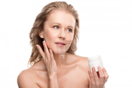 Foto de Beautiful mature woman with perfect skin applying cosmetic cream Isolated On White - Imagen libre de derechos