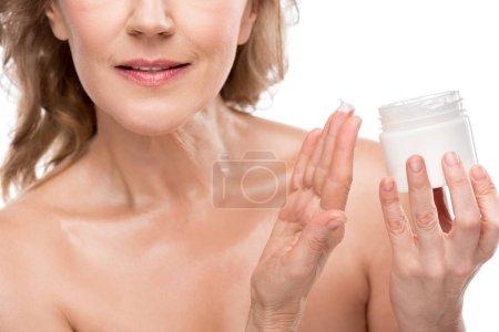 Photo pour Vue recadrée de femme mûre avec le récipient parfait de fixation de peau avec la crème cosmétique d'isolement sur le blanc - image libre de droit